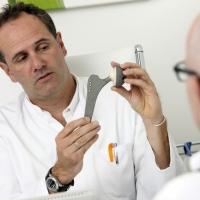 Arztpraxis. Maennlicher Patient im Gespraech mit einem Arzt. Arzt erklaert ihm die Funktionsweise eines kuenstlichen Hueftgelenkes.