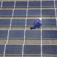 Bau einer grossen Photovoltaik Anlage auf mehreren Flachdaechern. Auf rund 16000 Quadratmetern Flaeche werden 4000 Solarmodule montiert. Das Solarkraftwerk soll eine Jahresleistung von 765000 Kilowattstunden erreichen, was den durchschnittlichen Jahresbedarf von 250 Haushalten entspricht. Gelsenkirchen, NRW, Deutschland, Europa.